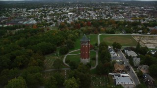 AX152_116 - 6K stock footage aerial video flying away from a water tower and cemetery among trees, autumn, Lawrence, Massachusetts
