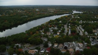 AX152_117 - 6K stock footage aerial video flying over town among fall foliage toward a river, autumn, Methuen, Massachusetts