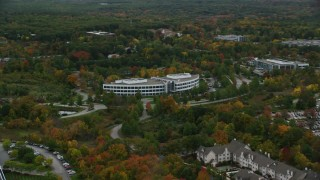 AX152_118 - 6K stock footage aerial video passing by an office building among fall foliage, autumn, Andover, Massachusetts