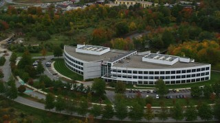 AX152_119 - 6K stock footage aerial video approaching an office building and trees with fall foliage, Andover, Massachusetts