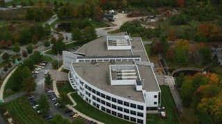 AX152_120 - 6K stock footage aerial video orbiting away from an office building and fall trees, Andover, Massachusetts