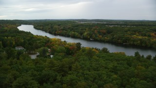 AX152_121 - 6K stock footage aerial video flying over trees with fall colors toward a river with kayakers, autumn, Andover, Massachusetts