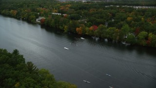 AX152_122 - 6K stock footage aerial video flying over kayakers and rowers in a river lined with partial fall foliage, Andover, Massachusetts