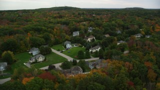 AX152_123 - 6K stock footage aerial video flying by upscale homes among trees with fall foliage, Andover, Massachusetts