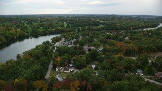 AX152_124 - 6K stock footage aerial video of waterfront homes and businesses along the river and autumn trees, Dracut, Massachusetts