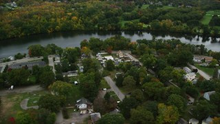 AX152_125 - 6K stock footage aerial video flying away from waterfront homes and trees with fall foliage along a river, Dracut, Massachusetts
