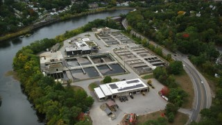 AX152_126 - 6K stock footage aerial video flying over water treatment plant along a river, autumn, Lowell, Massachusetts