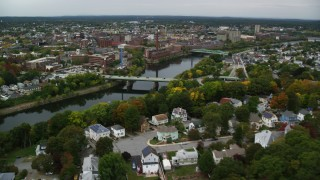 AX152_127 - 6K stock footage aerial video flying over town toward bridge spanning a river, approaching a hospital, Lowell, Massachusetts
