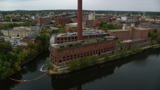 AX152_129 - 6K stock footage aerial video flying by riverside abandoned factory and smoke stack, autumn, Lowell, Massachusetts