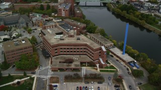 AX152_133 - 6K stock footage aerial video flying by Saints Medical Center near the river, blue smoke stack, autumn, Lowell, Massachusetts