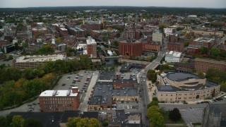 AX152_134 - 6K stock footage aerial video flying over a canal toward factory buildings, autumn, Lowell, Massachusetts