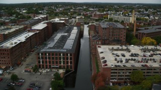 AX152_135 - 6K stock footage aerial video following a canal lined with factory buildings, autumn, Lowell, Massachusetts