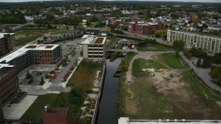 AX152_136 - 6K stock footage aerial video flying over canal toward locks and dam, autumn, Lowell, Massachusetts