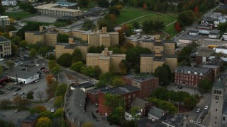 AX152_139 - 6K stock footage aerial video flying by urban apartment buildings among partial fall foliage, Lowell, Massachusetts
