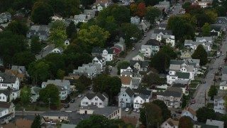 AX152_143 - 6K stock footage aerial video flying over urban neighborhood and trees with partial fall foliage, Lowell, Massachusetts