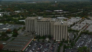 AX152_145 - 6K stock footage aerial video orbiting away from an office building and parking lots, autumn, Lowell, Massachusetts