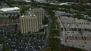 AX152_146 - 6K stock footage aerial video orbiting office building and parking lots, autumn, Lowell, Massachusetts