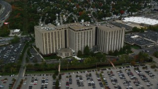 AX152_147 - 6K stock footage aerial video office building along parking lots and trees with fall foliage, Lowell, Massachusetts