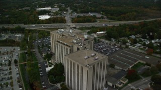 AX152_148 - 6K stock footage aerial video flying over and away from an office building, autumn, Lowell, Massachusetts
