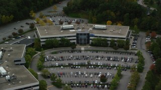 AX152_150 - 6K stock footage aerial video tilting down on office building and parking lot among fall foliage, Chelmsford, Massachusetts