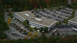 AX152_151 - 6K stock footage aerial video tilting up and away from office building nestled among fall foliage, Chelmsford, Massachusetts