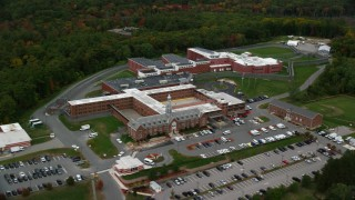 AX152_154 - 6K stock footage aerial video orbiting away from a prison among trees, autumn, Billerica, Massachusetts