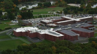 AX152_157 - 6K stock footage aerial video of  side view orbiting a prison surrounded by trees, autumn, Billerica, Massachusetts