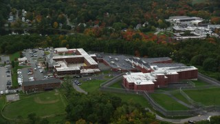 AX152_158 - 6K stock footage aerial video flying away from a prison backed by fall foliage, Billerica, Massachusetts