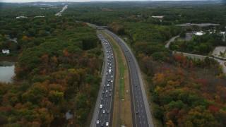 AX152_161 - 6K stock footage aerial video following a highway toward an overpass among fall foliage, Billerica, Massachusetts