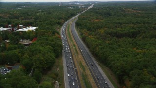 AX152_162 - 6K stock footage aerial video flying over highway bordered by fall foliage toward an overpass, Billerica, Massachusetts
