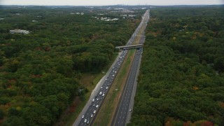 AX152_163 - 6K stock footage aerial video flying over overpass and highway among partial fall foliage, Bedford, Massachusetts