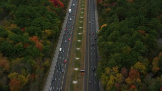 AX152_164 - 6K stock footage aerial video following a highway surrounded by fall foliage, Bedford, Massachusetts