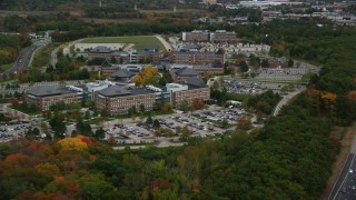 AX152_165 - 6K stock footage aerial video flying by parking lots and office buildings among fall foliage, Burlington, Massachusetts
