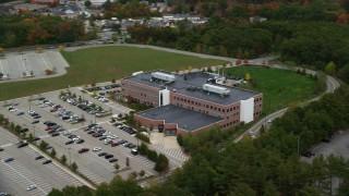 AX152_166 - 6K stock footage aerial video orbiting away from an office building and parking lot, autumn, Burlington, Massachusetts