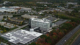 AX152_167 - 6K stock footage aerial video flying away from office buildings and parking lots, autumn, Burlington, Massachusetts