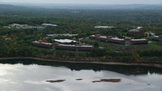 AX152_174 - 6K stock footage aerial video flying by office buildings, colorful foliage on waterfront, autumn, Waltham, Massachusetts