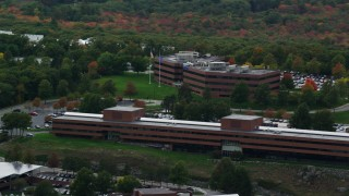 AX152_175 - 6K stock footage aerial video flying by office buildings, colorful foliage, autumn, overcast, Waltham, Massachusetts