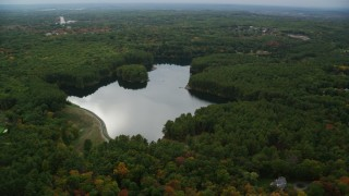 AX152_176 - 6K stock footage aerial video flying by Weston Reservoir, colorful foliage, autumn, Weston, Massachusetts