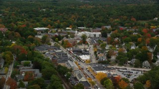 AX152_186 - 6K stock footage aerial video flying by church and shops along busy streets in autumn, Wellesley, Massachusetts