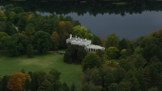 AX152_187 - 6K stock footage aerial video flying by mansion near the lake, autumn, Wellesley, Massachusetts