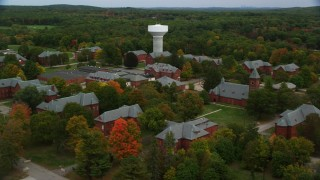 AX152_194 - 6K stock footage aerial video of a side view of Medfield State Hospital and water tower among fall foliage, Medfield, Massachusetts
