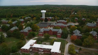 AX152_195 - 6K stock footage aerial video orbiting Medfield State Hospital among fall foliage, autumn, Medfield, Massachusetts