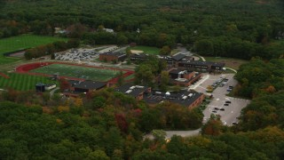 AX152_205 - 6K stock footage aerial video flying away from high school and football field among fall foliage, Dover, Massachusetts