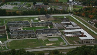 AX152_212 - 6K stock footage aerial video approaching Massachusetts Correctional Institution at Norfolk, surrounded by fall foliage, Massachusetts