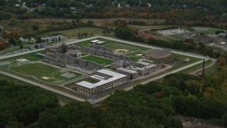 AX152_213 - 6K stock footage aerial video flying high over Massachusetts Correctional Institution at Norfolk, with autumn trees, Massachusetts