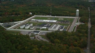 AX152_216 - 6K stock footage aerial video flying away from Massachusetts Correctional Institution Cedar Junction and fall trees, autumn, Walpole, Massachusetts