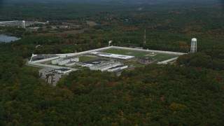 AX152_217 - 6K stock footage aerial video flying away from Massachusetts Correctional Institution Cedar Junction, over fall foliage, Walpole, Massachusetts