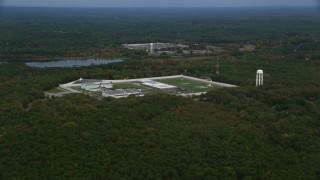 AX152_218 - 6K stock footage aerial video of a wide view of fall foliage approaching Massachusetts Correctional Institution Cedar Junction, Walpole, Massachusetts