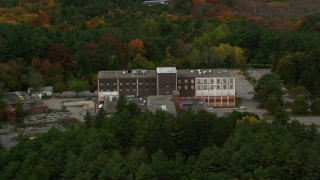 AX152_219 - 6K stock footage aerial video flying over fall foliage toward abandoned hospital, Walpole, Massachusetts