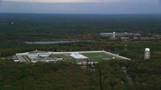AX152_223 - 6K stock footage aerial video of a high view passing by Massachusetts Correctional Institution Cedar Junction among fall foliage, Walpole, Massachusetts